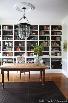 home office & library with farmhouse table, bookshelves, and lantern