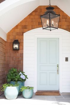 Charming entry with an oversized hanging lantern & two lanterns framing the beautifully painted front door