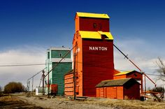 The orange and green Pioneer grain elevators on a sunny day in the town of Nanton, Alberta, Canada. Print Pictures, Cool Pictures, Beautiful Pictures, Canadian Prairies, Grain Silo, Wooden Barn, Canada Eh, Sky Landscape, Old Barns