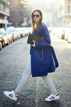 Choose a blue coat and grey skinny pants if you're going for a neat, stylish look. Want to go easy on the shoe front? Rock a pair of white and black low top sneakers for the day.  Shop this look for $148:  http://lookastic.com/women/looks/clutch-coat-skinny-pants-low-top-sneakers-sunglasses/4423  — Black Leather Clutch  — Blue Coat  — Grey Skinny Pants  — White and Black Low Top Sneakers  — Navy Sunglasses