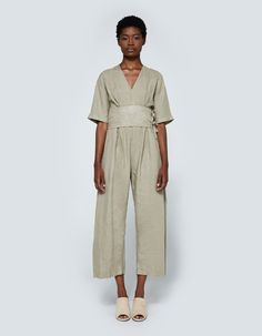 Jumpsuit from Black Crane in Shetland. Deep V-neckline. Long slit at back with button-and-loop closure. Short dolman sleeves. Thick waistband with self-tie belt. On-seam side pockets. Relaxed straight leg. Full-length. Casual fit.   • Gauze • 100% line