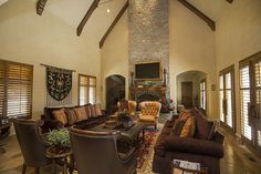 This huge living room features vaulted ceiling with exposed beams, ornate leather chairs in light and dark tones, chocolate colored twin couches, and a stone hearth reaching to the ceiling.