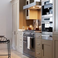 Building in appliances to your cabinetry is a sure way to keep a compact space looking sleek. Here, a range cooker takes the central spot in a single row of hand-painted tulipwood units, while a coffee machine, oven and warming drawer form a functional bank.