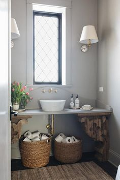 Exquisitely styled cottage bathroom is lit by mirror tiled sconces mounted to a gray wall on either side of a leaded glass window finished with black moldings.