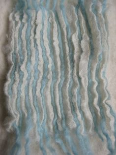 Op een stukje wol-etamine heb ik lichtblauwe wollen draden gelegd. Met een katoenen draad heb ik over deze draden heen geregen. De katoenen ...