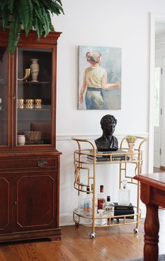 Mix up your home decor with a traditional wood hutch sitting near a glam brass bar cart.