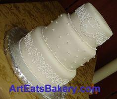 Three tier wedding cake with monogram, pearls and scolls