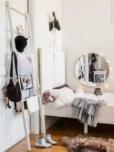 Little girls room- white bed, white ladder for hanging storage, round mirror above bed, string lights, all white