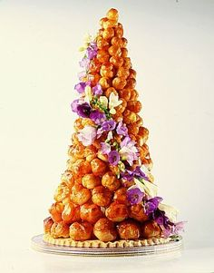 Croque en bouche with fresh purple flowers drizzle with white choc to