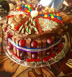 First time making a CandyCake :) three layers of cake, separated by strawberry jelly, covered in chocolate frosting and dressed with a variation of candies(kitkat, twix, twizzlers, sprinkles, mnms and cheers, Hershey's kisses, grapes and a marshmallow) #chefamy #trinidad #birthdaycake