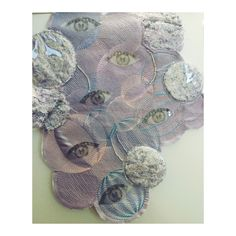 Appliquéd amaya machine embroidery, combined with acetate bead embellishments created through taking photographs of my own iris and pupils. Layered tufting created through combining silk polyester threads beneath acetate created contrasting surface textures to combine with contour stitching.