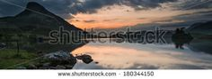 Panorama landscape stunning sunrise over lake in mountain range - stock photo