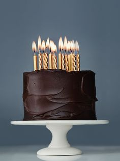 Simple, elegant, homemade chocolate birthday cake with gold candles.