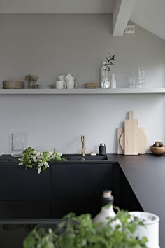 Black stained wood kitchen cabinets | black kitchen cabinets | gold kitchen sink tap |minimalist kitchen | single shelf above the kitchen sink for displaying crockery, tableware, vases | stacked wooden chopping boards in different shapes and sizes | white spring flowers | natural accessories | Spring feeling in the kitchen - Stylizimo