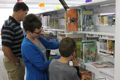 From left: Jon, Missy and Owen Schwebach look at books in the newly renovated Ames Public Library. The library re-opened for business on Sunday and a crowd of hundreds gathered to be the first to read and check out books in the renovated building. Photo by Julie Ferrell/Ames Tribune