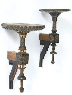 TWO CARLO BUGATTI (1856-1940), MILAN, WALL BRACKETS Last quarter 19th century. Each bracket is walnut, oak, and ebonized wood and has circular shelves on turned supports. They feature pierced, hammered and stamped sheet copper overlay decoration, the larger with a vellum-covered shelf and bone dentil detail. Height 53.0 cm. (21 7/8 in.) and smaller.