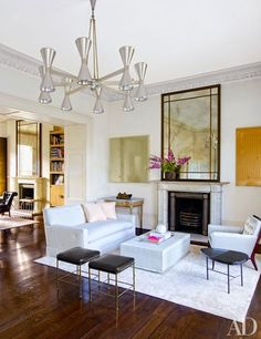 Damien Hirst butterfly paintings flank a bespoke mirror by Veere Grenney Assoc. above the drawing room's fireplace | archdigest.com