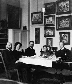 Henri Matisse (center) and Hans Purrmann (right) dining with Michael, Sarah, and Allan Stein at their apartment at 58 rue Madame, Paris, circa 1908. The paintings in the background, all by Matisse, are The Young Sailor I (far left); Pink Onions and Male Nude (left column); Fruit Trees in Blossom, Woman in a Kimono, Nude Reclining Woman, and Nude before a Screen (center column); Madame Matisse in the Olive Grove, a sketch for Le Bonheur de Vivre, and Madame Matisse (The Green Line) (right…