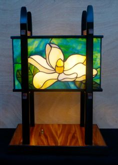 """An Asian-inspired table lamp with a unique magnolia blossom on each side, The base is a dramatic piece of Australian Red Cedar trimmed with African Wenge.  The uprights are African Mahogany in black lacquer.  This piece stands about 21"""" high."""