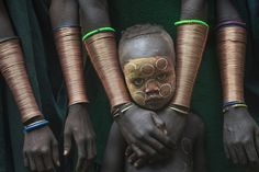 A young boy stands among Suri women wearing copper bracelets in Kibish Ethiopia. The image was taken by Danny Yen Sin Wong of Malaysia who won the title of best single image in the 'faces, people, cultures' category Photographie National Geographic, National Geographic Photography, National Geographic Photo Contest, Population Du Monde, Cool Pictures, Cool Photos, Amazing Photos, Funny Pictures, Photographs Of People