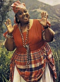 A respected and highly mourned entertainer across the West Indies. Miss Lou hailing from Jamaica wearing the traditional plaid print. She is one of the greatest satirist of yesteryear. Jamaican People, Jamaican Women, Jamaican Art, Jamaican Music, Jamaican Recipes, Bolivia, Uganda, Jamaica National, Jamaica History