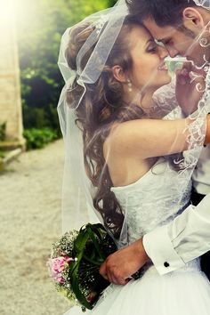 such a cute picture. under the veil. He's holding her bouquet