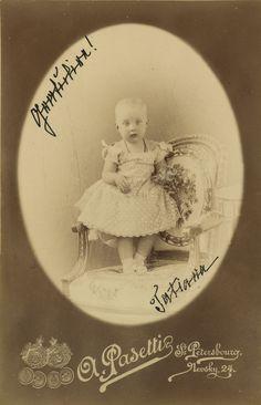 Princesa Tatiana Constantinovna como uma criança pequena. Ela está em pé em uma cadeira com um bordado de motivos florais e está vestindo um vestido de renda e um colar. 1891.