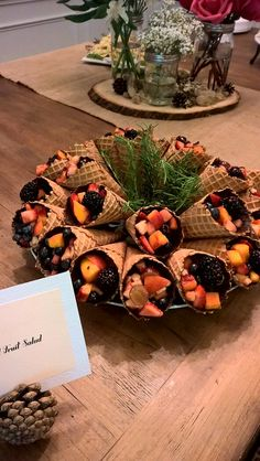 Waffle cones with chocolate inside, filled with fruit for woodland baby shower.