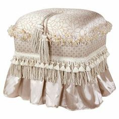 """Upholstered ottoman with a tassel trim and ribbon fringe.  Product: OttomanConstruction Material: Polyester and woodColor: CreamDimensions: 20"""" H x 16"""" W x 10"""" D"""