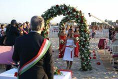 Un Sì #romantico sulla spiaggia tra fiori bianchi e rossi