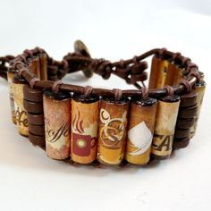 Can't live without your morning cup of coffee? Now you can show that love (addiction?) all day long with this fun and funky coffee cuff bracelet!! Each bead has a different design in shades of gold, tan, and brown, adding to the uniqueness!! These EP Beads are 20x7mm wood tubes handwrapped with coffee related graphics, then triple coated to ensure water resistance (but please keep them as dry as possible). Along with brown wood discs, they are laced with 1mm brown hemp onto 2mm brown…