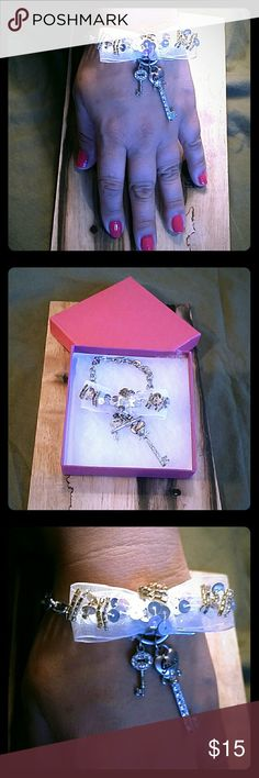 GUESS BLINGY KEYS SILVER COLORED BRACELET GUESS BLINGY BOW & 2 KEYS SILVER COLORED BRACELET, in good pre-loved condition sold as is,  some very light fading.. but hardly noticeable.  Please look at pictures. Guess Jewelry Bracelets