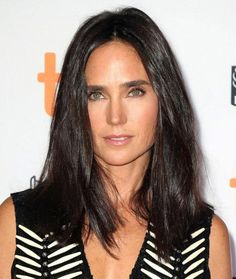 Jennifer Connelly made sure that she would get plenty of attention by dressing up in a quirky and stylish multi colored and abstract printed dress with a demure neckline and asymmetrical hemline that mostly grazed her upper thighs except a column on left side that reached down to floor, while walking the red carpet at the HFPA & InStyle's Celebration held during the 2016 Toronto International Film Festival at Windsor Arms Hotel on September 10, 2016 in Toronto, Canada.