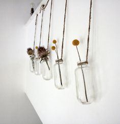 Row of hanging bottles with dried flowers