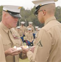 Oldest Marine present, Sgt. Maj. Conrad Potts, sergeant major, Marine Corps Logistics Base Albany, passes a slice of cake to the youngest Marine present, Lance Cpl. Cree Gaines, administrative specialist, Military Personnel, MCLB Albany, Wednesday, during the Marine Corps' 238th birthday cake-cutting ceremony and uniform pageant held in front of Building 3500, here. (Photo by Nathan L. Hanks Jr.)