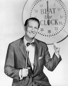 Bud Collyer as the host of the television program Beat the Clock.