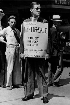 """Robley D. Stevens, 30-year-old victim of the Depression, wears a sign that reads: """"I am for sale. I must have work or starve,"""" while standing on a sidewalk in Baltimore, Md., in Aug. 1931."""
