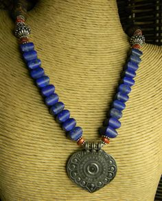 Luscious lapis lazuli necklace design with an artisan silver focal pendant from India. Red jasper, Tibetan agate provide a striking contrast to the deep blue lapis stones, and Sterling silver accent beads, spacers and toggle clasp are the perfect finishing touches. The length of the necklace is 17 inches, plus a 1 3/4 inch pendant drop.