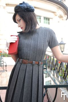 """--""""A grey flannel dress of strict form. It is decorated with large pleats on the front only, with a belt of  loden green leather. This dress is reminiscent of the uniform worn by Schiaparelli sales girls in the 1920s. It also evokes the schoolgirl style, made fashionable at the time by the film Gigi. Pill box style hat in black lacquer braided straw and red kid cover purse decorated with a wide zipper, a Schiaparelli license sold in the USA and also in her Boutique ... photo BillyBoy…"""