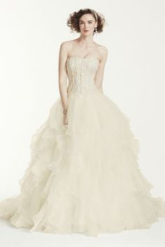Picture your guests' reactions when you arrive in this show-stopping organza and lace bridal gown. Priced at an incredible special value, this strapless dress wows thanks to corset detailing, beaded Venise lace appliques, and a dramatic ruffled skirt with chapel train. You'll feel like a living fairytale as you walk down the aisle in this graceful, elegant style.  Oleg Cassini, exclusively at David's Bridal.  Also available in Plus Size, Petite, Extra Length and Extra Length Plus Size.