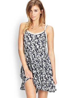 Bring out your inner flower child! This tiered smock dress features a floral print and cutout bac...