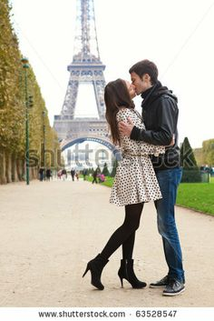 Young romantic couple kissing near the Eiffel Tower in Paris - stock photo