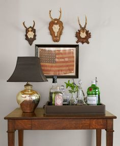 The 1915 flag in this home's entryway is a find from the Brimfield Antique Show. A vintage mercury-glass lamp and hunting trophies add to eclectic look.