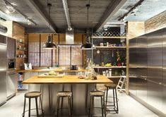 cuisine industrielle aménagée avec des appareils électroménagers en inox, îlot central en bois et inox et tabourets de bar en métal et bois