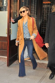 Kate Hudson flexes her expert styling—pairing a crisp suede trench with her Joie flares and printed blouse for a modern touch.