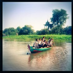 Children riding a boat to school in the floating village of Kompong Khleang, Cambodia
