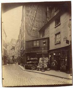 "Eugène Atget : rue Galande, 1899, Paris Vè; shop selling vegetables. Sign on the wall ""Chapellerie 9 rue St Jacques"""