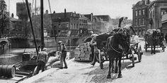 1929. Nieuwekade, Wijk C. Laden van een schip. Met de Watertoren en de Weerd- en Zandbrug