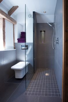 Our client wanted their bathroom in a converted barn to loose the feel of an old farm house and become a stylish en-suite.The vanity unit with high gloss fronts sits nicely under the Italian his & her basins and taps. We created a walk in wet room shower..The contrast between old wood and a new bathroom brings the room to life, without making either stand out too much. The end result is a completely bespoke bathroom that uses the best of old and new.