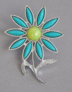 A pretty and fresh textured silver tone metal flower that features turquoise cabochon pedals framing a yellow pearlescent center called Daisy Time. Hallmarked SARAH COV on the back side. It measures 1